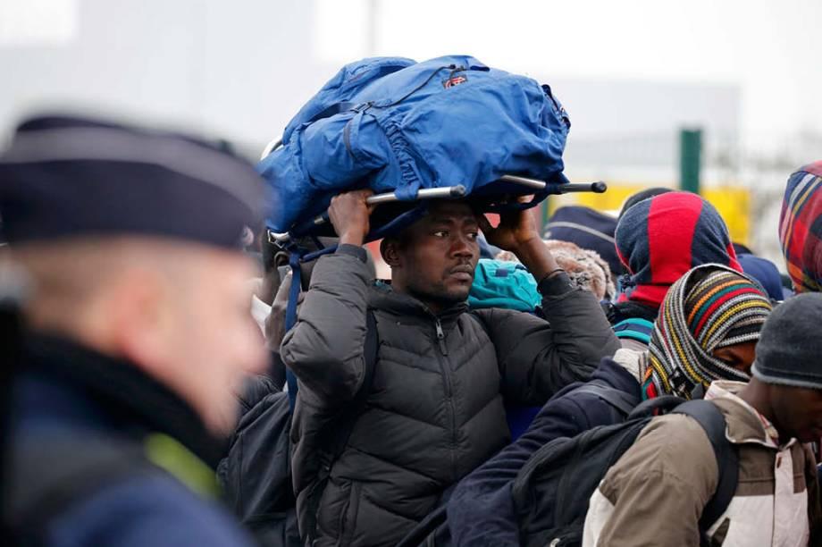 Refugiado com seus pertences na fila de desocupação do campo