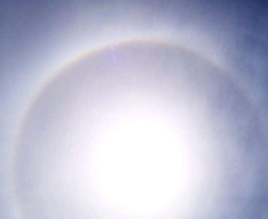 """Cirrostratus: estas nuvens se localizam logo abaixo das nuvens cirrus. São finas e leves, a ponto de não encobrirem o sol. Em vez disso, quando estão em frente ao Sol, formam o efeito """"halo"""", este círculo que pode ser visto na foto."""