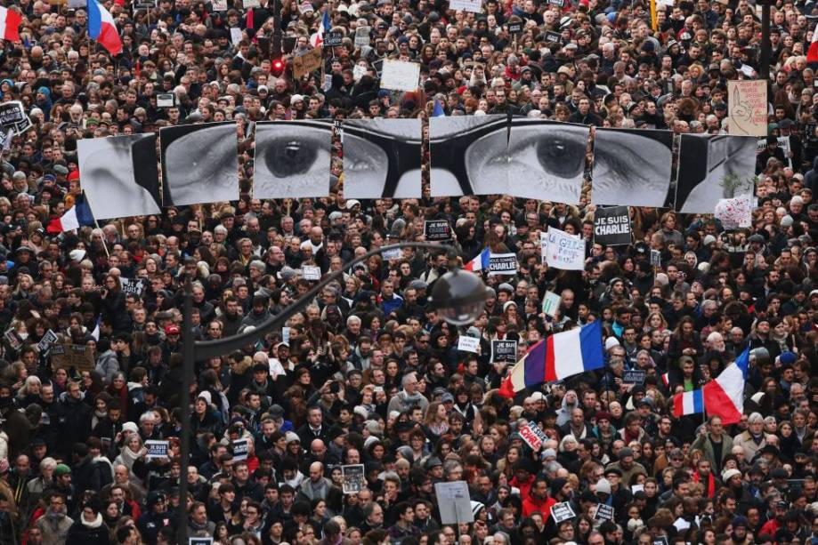 No dia 7 de janeiro,12 pessoas morreram e 11 ficaram feridas em um tiroteio em Paris.O grupo extremista Al Qaeda na Península Arábica (AQPA), com base no Iêmen, assumiua responsabilidade pelo ataque terrorista ao semanário satírico francês <em>Charlie Hebdo</em>.O ataque ao <em>Charlie</em> foi o início de três dias de terror na França, que ainda presenciou o assassinato de uma policial e umsequestro com vítimas fatais em um supermercado em Paris. Ao todo, dezessete pessoas foram assassinadas pelos terroristas.Dias depois, pessoas de toda a França se reuniram para protestar. Na foto, os cartazes que montam a imagem de um rostoé uma homenagem ao cartunistaGeorges Wolinski, que foi morto.