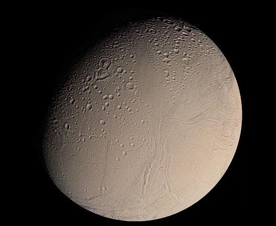 Esta é Encélado, uma das luas de Saturno. Imagens da sonda Cassini indicam que existam reservatórios de água líquida abaixo da crosta gelada do satélite. A água seria expelida à superfície por meio de gêiseres de vapor e gás.