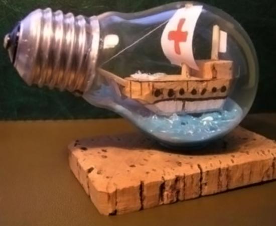 Já esta lâmpada queimada foi usada para abrigar uma escultura de barco.
