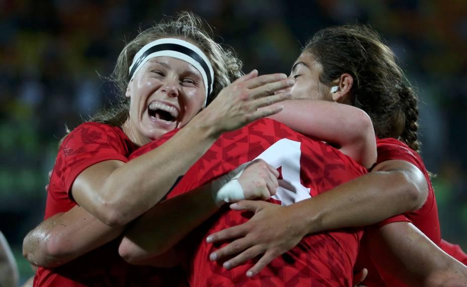 """O Canadá já compete no rúgbi masculino desde a Olimpíada de 1924. Mas, para o time feminino, os Jogos Olímpicos de 2016 são os primeiros - mesmo que as jogadoras já tenham provado o quanto são boas no esporte: ganharam pelo menos uma medalha a cada competição mundial em que participam. Aqui no Brasil, não foi diferente: na segunda (8), o time canadense derrotou a Grã-Bretanha e conquistou o bronze na final. A loira sorridente da foto é Kelly Russell, que abraça as companheiras de time depois da vitória. Em entrevista, a capitã das canadenses, Jen Kish, disse """"Me sinto como uma super heroína, e tenho certeza que as minhas companheiras se sentem do mesmo jeito. É maravilhoso""""."""