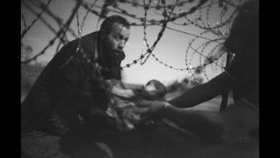 """Um homem passa um bebê por uma cerca na fronteira entre a Hungria e a Sérvia. A imagem, do australiano Warren Richardson, retrata um momento de esperança em meio à trágica crise dos refugiados sírios que tentam escapar do Estado Islâmico. A foto foi considerada """"a imagem do ano"""" pelo World Press Photo."""