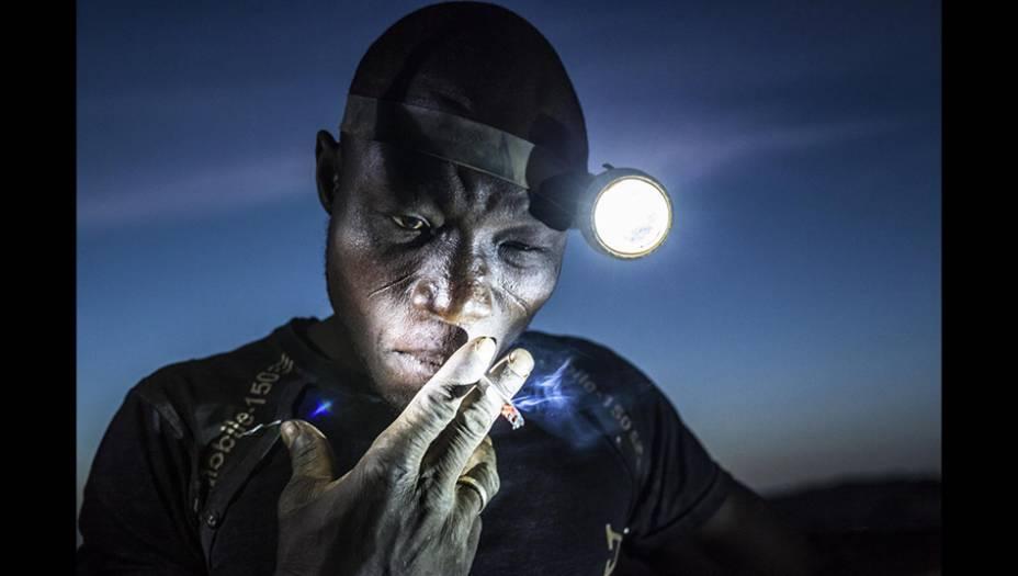 """Depois de horas de trabalho em condições terríveis, exposto a metais pesados e a químicos tóxicos, um mineiro de Burkina Faso tira uma folga, aspirando um pouquinho mais de substâncias venenosas. A foto, do esloveno Matjaz Krivic, foi ironicamente batizada de """"Cavando o Futuro"""", e levou o segundo prêmio na categoria Gente."""