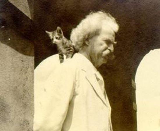 Mark Twain posa com seu gatinho no ombro. O escritor e humorista é conhecido pelos romances As Aventuras de Tom Sawyer e As Aventuras de Huckleberry Finn.