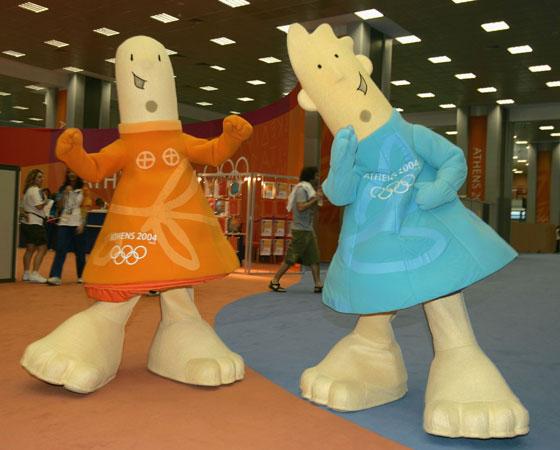 ´Athena e Phevos´ - Jogos Olímpicos de Atenas (2004): Os dois mascotes foram feitos por Spyros Gogos e são bonecos que imitam crianças. Os dois mascotes irmãos tiveram o design baseado em um antigo boneco grego de terracota. Além disso, ´Athena´ é a deusa da sabedoria e ´Phevos´ seria o deus da luz e da música.
