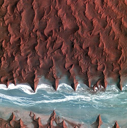 Essa foto extraordinária mostra o deserto da Namíbia, na África. A parte em azul é o rio Tsauchab, que permanece seco durante boa parte do ano. Os pequenos pontos negros perto do rio são diferentes tipos de vegetação.