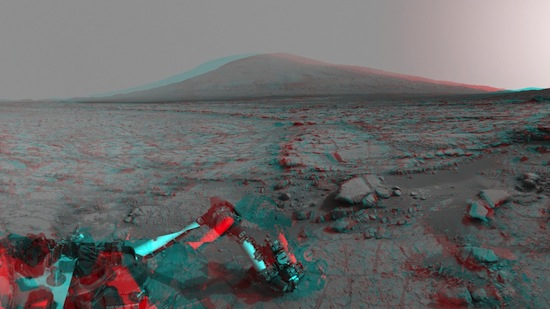 A imagem dessa cratera em Marte foi tirada do Curiosity Rover Mount Sharp. Dentro da cratera, uma montanha de 5km domina o horizonte. Em primeiro plano, o braço robótico da sonda utiliza uma ferramenta para explorar o solo do planeta vermelho.