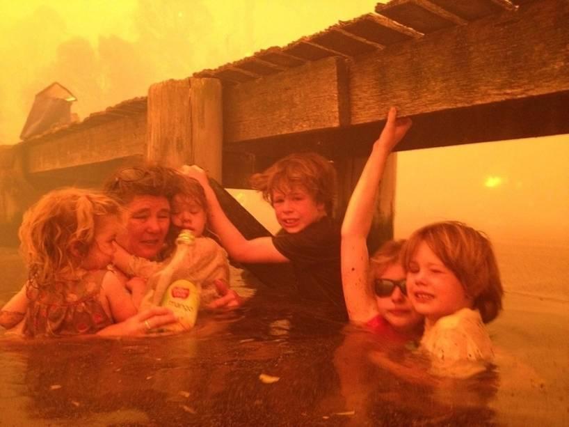 Tammy Holmes e seus netos se protegem em um cais fugindo de umincêndio florestal que se alastrou até a cidadeaustraliana de Dunalley. O fotógrafo é o avô das crianças, Tim Holmes, que decidiu levá-los para água.