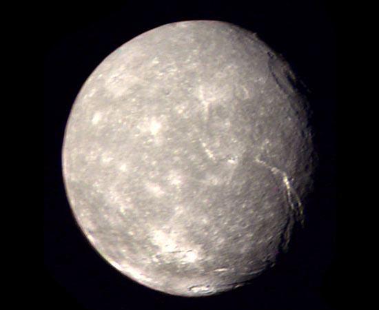 Esta é Titânia, a maior lua de Urano. Sua superfície é cheia de cânions e escarpas. As únicas imagens disponíveis foram tiradas em 1986, durante a missão da sonda espacial Voyager 2. Por isso, apenas 40% do satélite foi mapeado.