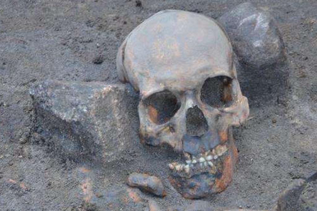 """A cabeça deste esqueleto foi achada longe do corpo, """"imobilizada"""" entre duas pedras"""