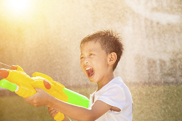 happy little boy yelling and playing water guns in the park