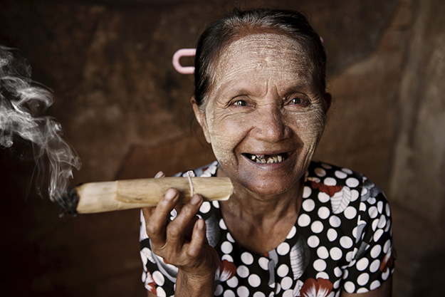 Happy old wrinkled Asian woman smoking