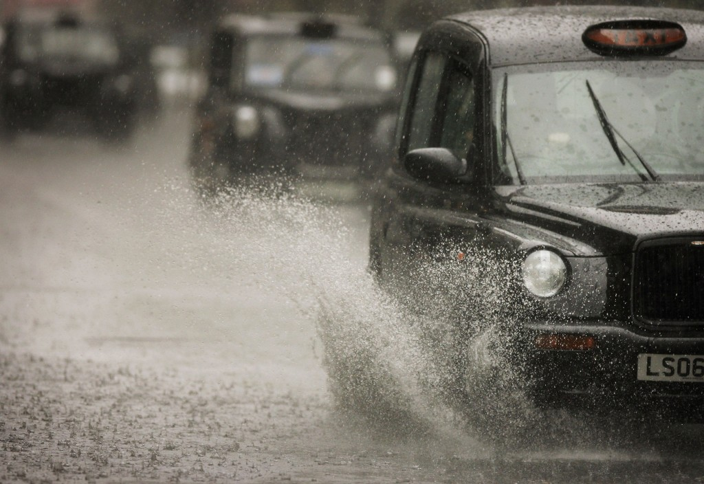 "LONDON - JUNE 13: A London ""Black Cab"" taxi drives through a patch of standing water after a heavy downpour on June 13, 2006 in London. (Photo by Bruno Vincent/Getty Images)"