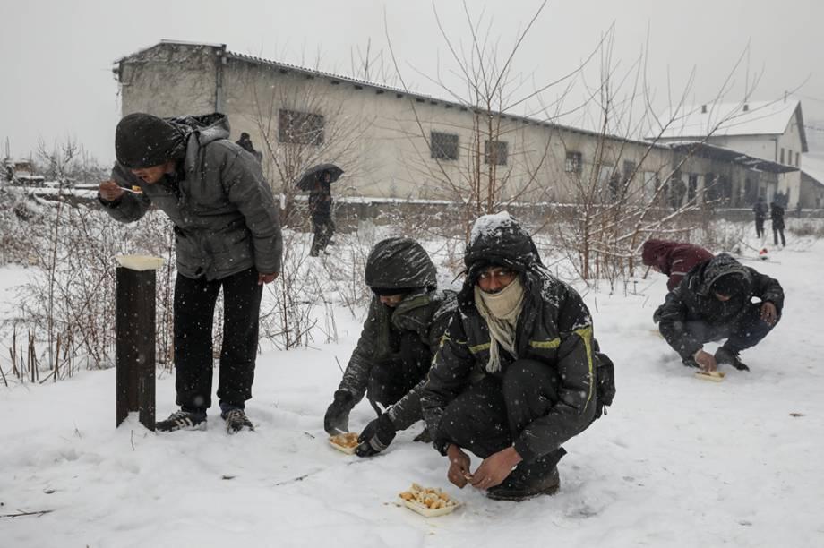 Imigrantes comem o prato de comida que receberam a céu aberto enquanto a neve cai em Belgrado.