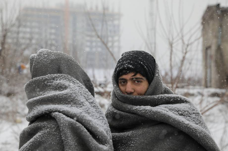 Refugiados tentam se proteger do frio em Belgrado.