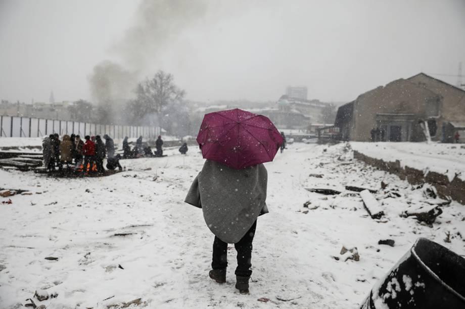 Um grupo de pessoas acende uma fogueira perto da estação de trem em Belgrado.