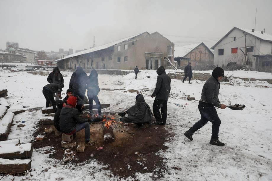 Enquanto a neve cai, refugiados tentam se esquentar em Belgrado.