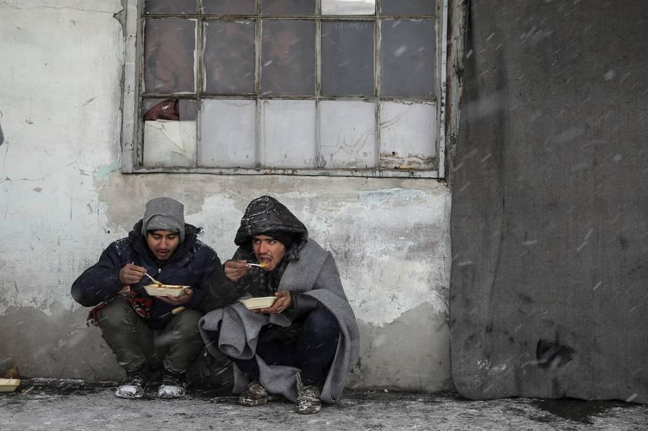 Dois homenstentam se esconder do vento enquanto comem.