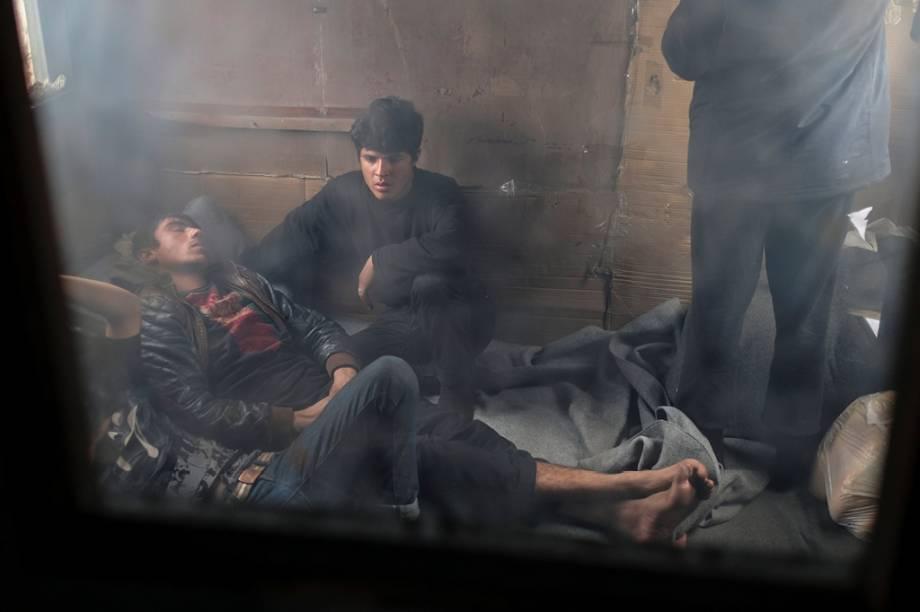 Imigrantes descansam dentro de um vagão abandonado.