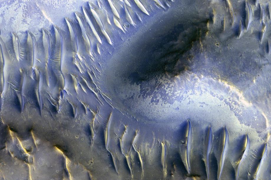 Isto é Marte. Essas ondinhas que aparecem abaixo, na verdade, são dunas de areia que são formadas por um vento que vai do norte (no canto esquerdo da foto) ao sul. A grande sacada da imagem é mostrar que uma montanha marciana, localizada no meio da foto, conseguiu bloquear essas correntes de vento, impedindo a criação das dunas na sua parte de trás.