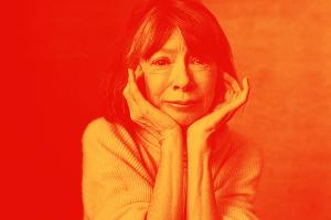 Joan Didion com a cabeça apoiada nas duas mãos.