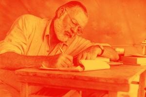 Foto de Hemingway, de óculos e barba branca, escrevendo à mão em uma mesa de madeira.
