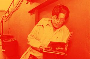Jovem Stephen King, de topete e óculos grandes, lendo de pé