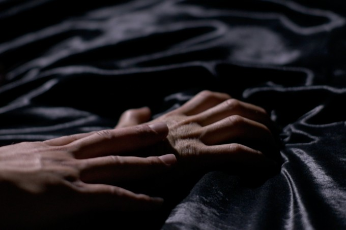 Close up of a man holding a woman's arms down in bed
