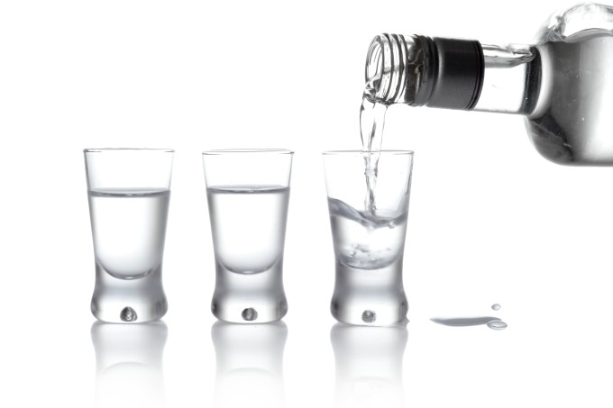 Bottle and glasses vodka poured into glass isolated on white