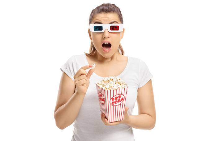 Scared girl with 3D glasses and popcorn