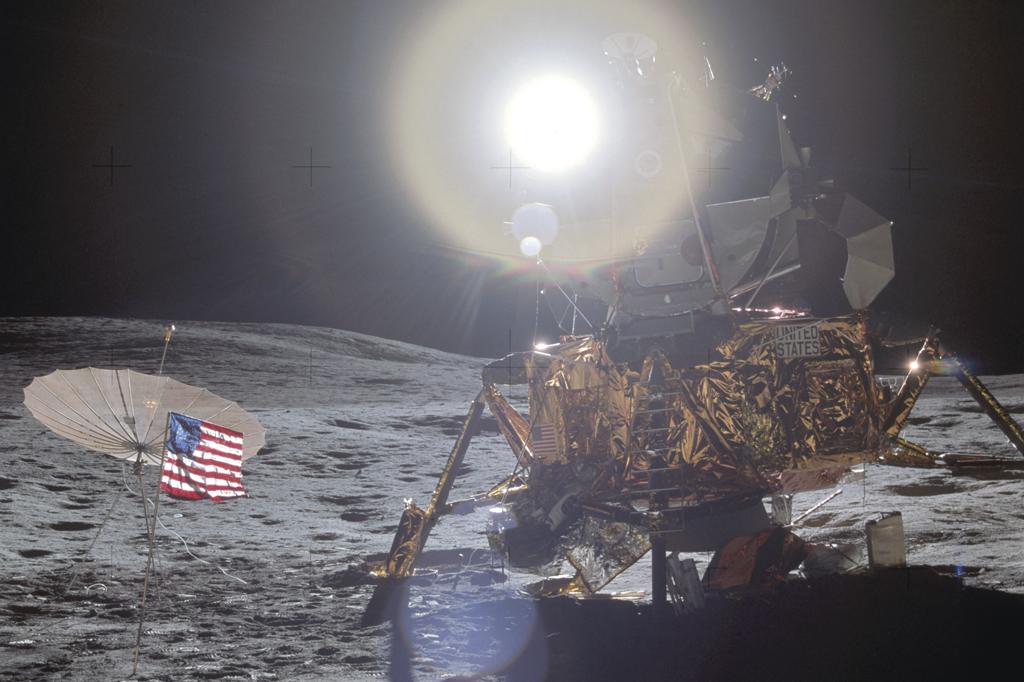 O módulo Antares, que pousou numa região com oito graus de inclinação. Ele é dourado, e há uma bandeira dos EUA hasteada à esquerda. Ao fundo, o Sol.