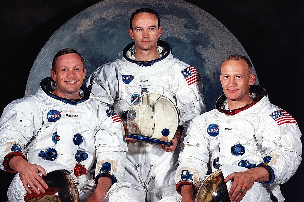 Da esquerda para a direita: Neil Armstrong, Michael Collins e Buzz Aldrin. A tripulação da Apollo 11. Eles estão com os trajes espaciais, com o capacete a tiracolo.