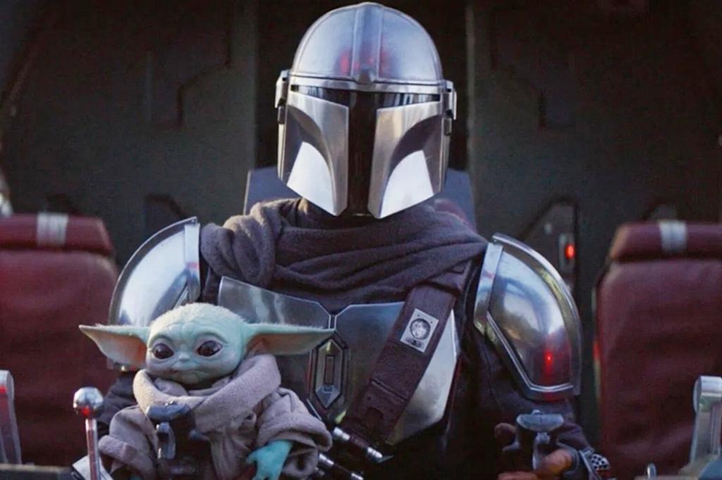 A imagem mostra uma pessoa usando uma armadura na cor cinza, com um capacete também na cor cinza e um visor em formato de T na cor preta. Ele carrega um Yoda, personagem da série Star Wars, pequeno, um ser da cor verde, com orelhas pontudas e olhos pretos, que usa uma roupa na cor cinza.