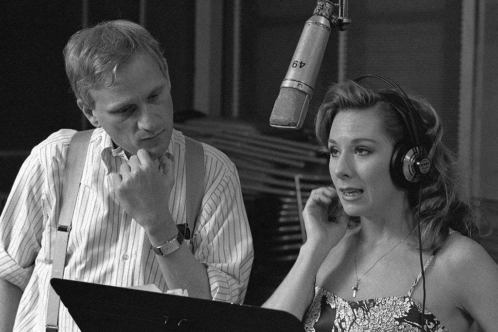 A imagem em preto e branco mostra um homem, usando uma camisa listrada e um suspensório olhando para baixo, como se estivesse lendo alguma coisa, ao lado de uma mulher de cabelos compridos, com headphones, que parece estar cantando, já que há um microfone em cima dela.