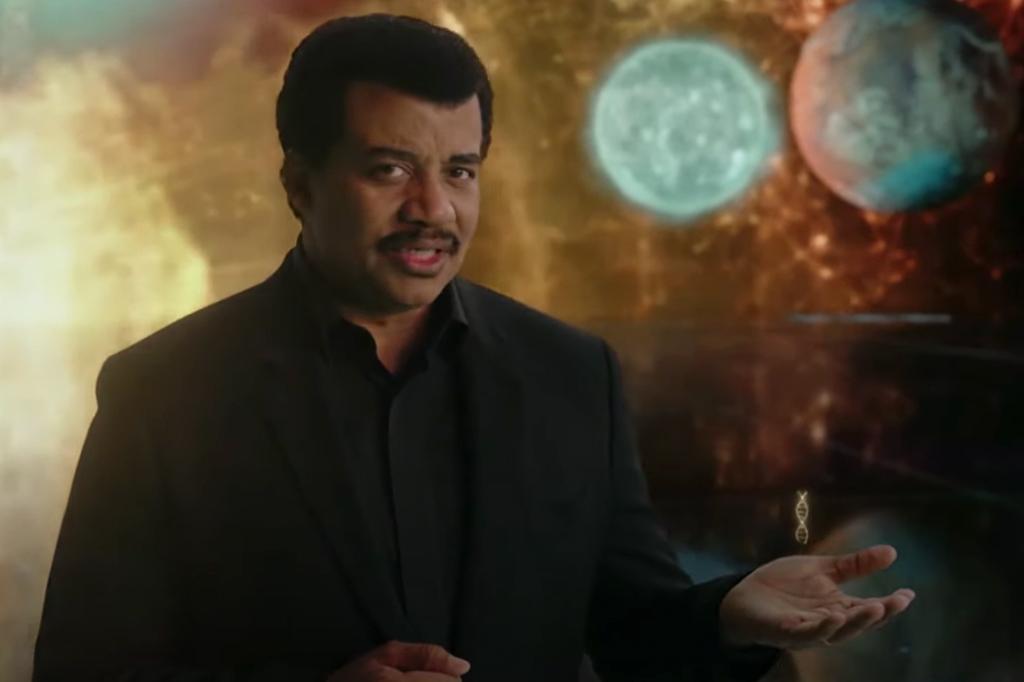 A imagem mostra um homem negro de cabelos curtos e escuros e bigode, usando uma camisa e um blazer preto em frente a um fundo que mostra o universo.