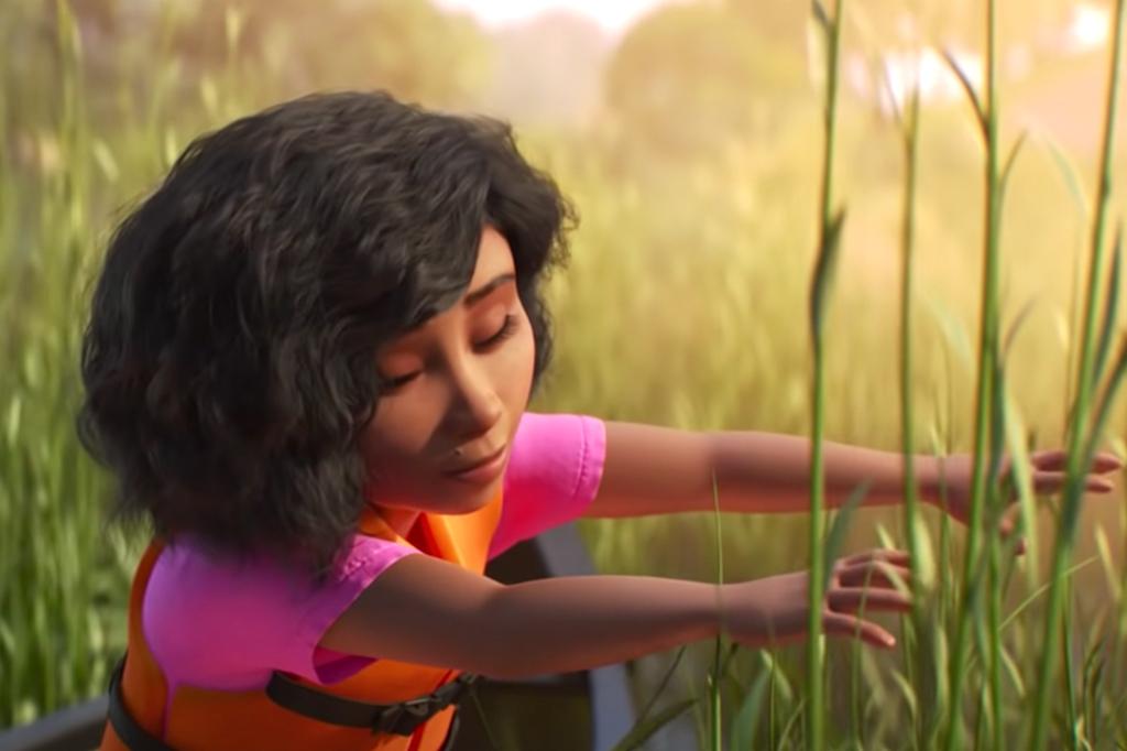 A imagem mostra a animação de uma menina negra, de cabelos escuros na altura dos ombros, ondulados, usando uma camiseta rosa com um colete salva-vidas laranja por cima. Ela está sentada no meio da grama e está esticando seu dois braços para tocá-la, enquanto os olhos estão fechados.