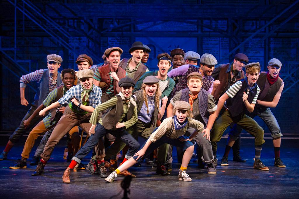 A imagem mostra um grupo de pessoas dançando em um palco. Todas usando vestimentas semelhantes: boina, camisas com coletes por cima, calças dobradas, meias altas e tênis.