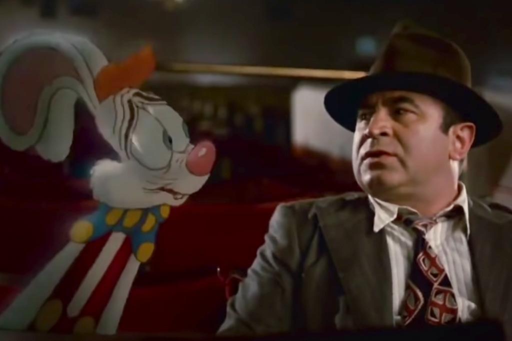 A imagem mostra uma cena do filme Uma Cilada Para Roger Rabbit, com um desenho de um coelho branco, com olhos verdes e um suspensório vermelho com uma gravata borboleta azul com bolinhas amarelas, olhando para um homem branco, que usa um chapéu marrom, uma camisa creme com uma gravata preta com detalhes em amarelo e vermelho e um blazer cinza.