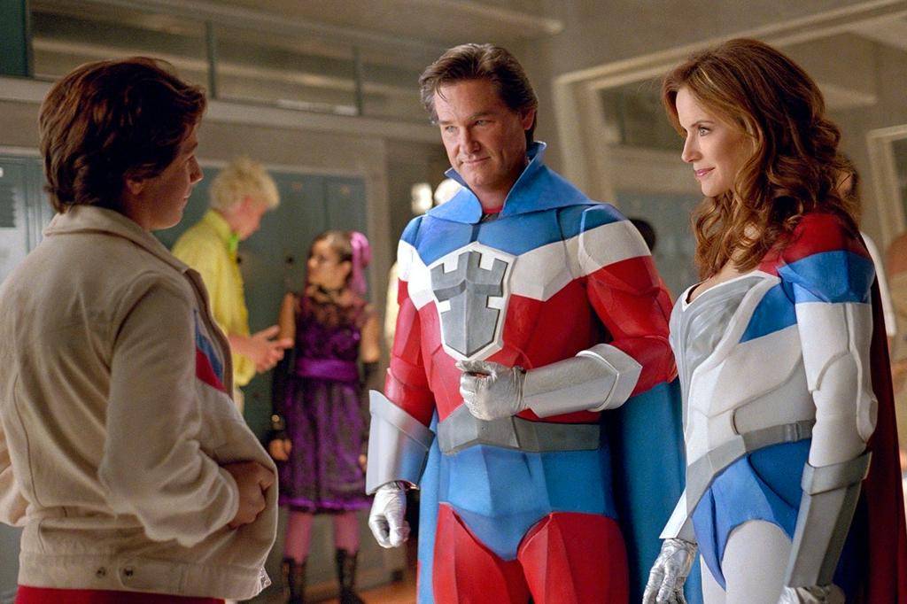 A imagem mostra uma cena do filme Sky High, com um menino branco de cabelos curtos e escuros virado de costas, usando uma jaqueta na cor creme, olhando para um homem e uma mulher brancos, usando vestimentas de super herói nas cores azul vermelho e branco no corredor de uma escola.