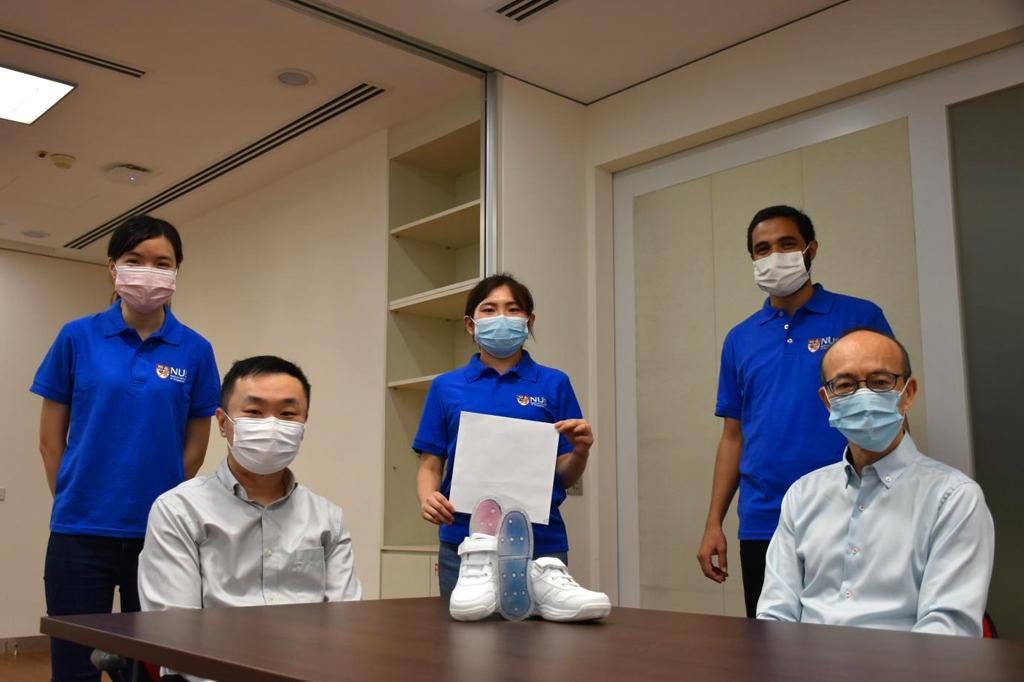 Cinco cientistas sentados em volta de uma mesa, que possui um par de tênis branco e palmilhas no centro.