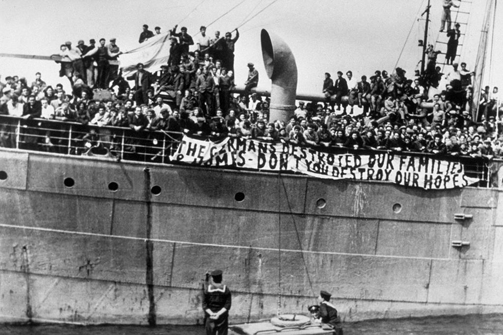"""Foto em preto de branco de um navio abarrotado de gente sendo ancorado no porto. São imigrantes judeus ilegais chegando à Palestina em 1947: """"Os alemães destruíram nossas famílias, não destruam nossa esperança"""", diz a faixa branca colocada no lado do navio."""