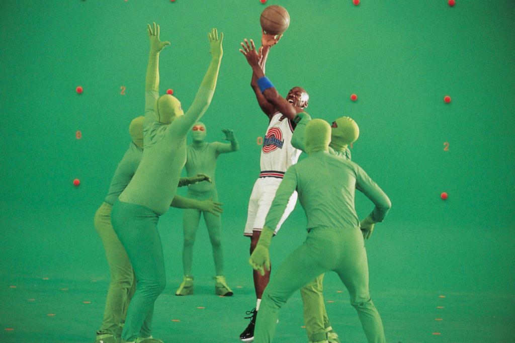 Foto de Michael Jordan filmando Space Jam ao lado de pessoas usando roupas verdes.