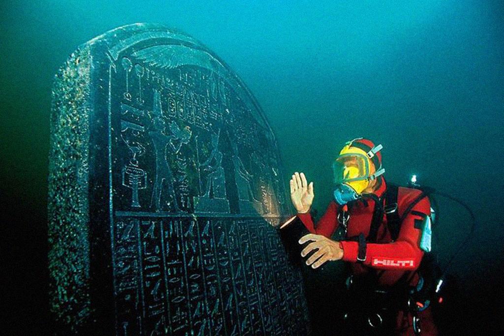 Foto de um mergulhador ao lado de um artefato encontrado na cidade submersa.