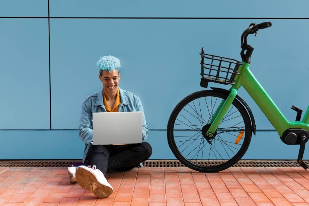 Homem sentado no chão ao lado de bicicleta verde enquanto usa Notebook Dell Inspiron 15 3000 Series.