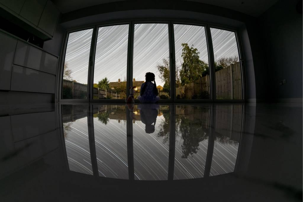 Foto de uma pessoa dentro de casa com o rastro das estrelas de fundo