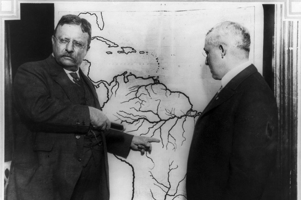 Theodore Roosevelt apontando local no mapa do Brasil durante expedição em Rondônia.